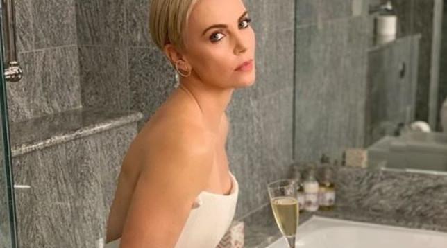 Charlize Theron beve champagne seduta sull'asse del water