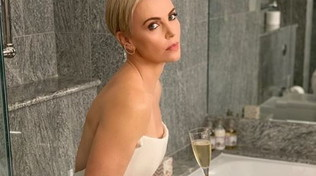 Charlize beve champagne sull'asse del water