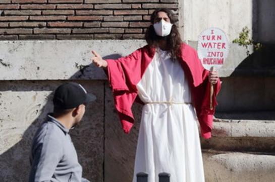 """Coronavirus, in una via di Roma compare Gesù con la mascherina e promette: """"Io trasformo l'acqua in amuchina"""""""