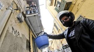 Nei vicoli di Napoli gruppi di scooteristi portano la spesa