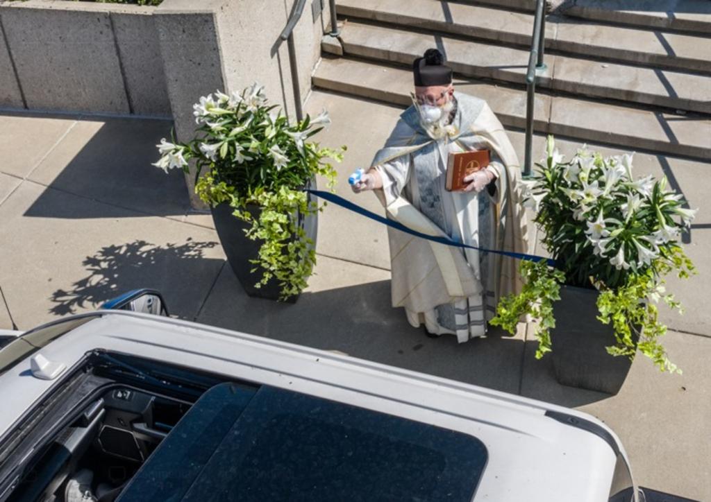 Coronavirus, negli Usa la benedizione del prete è a prova di distanziamento sociale