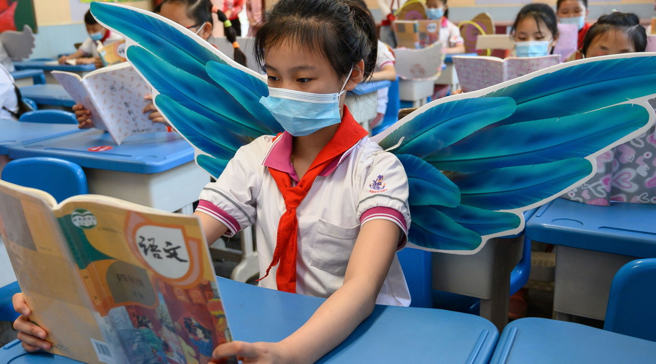 Cina, studenti indossano le ali per distanziarsi: l'iniziativa di una scuola elementare