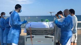 Coronavirus, medici e infermieri portano il paziente sul lungomare di Barcellona