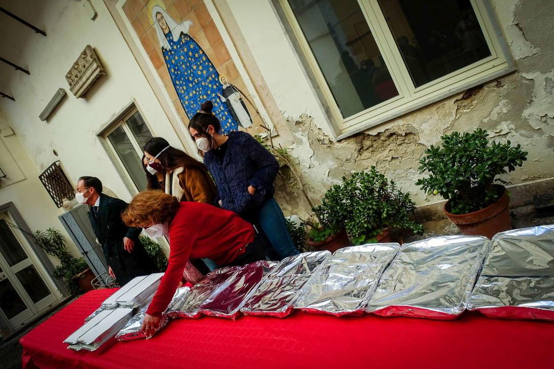 La comunità di Sant'Egidio prepara piatti di lasagna per i poveri